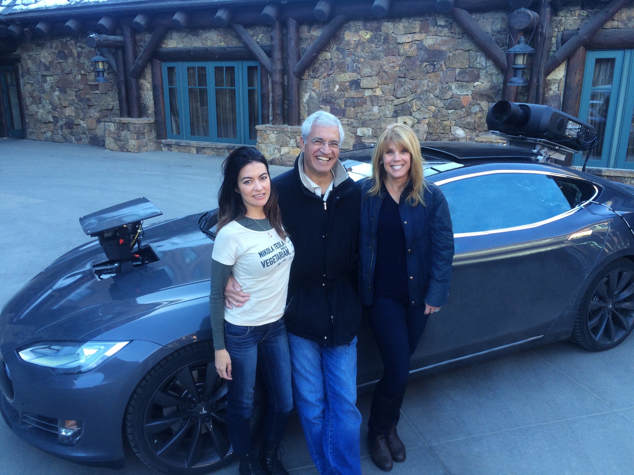 "Leilani Münter, Louis Psihoyos and Laura Turner Seydel standing by a one-of-a-kind Tesla made in partnership with Elon Musk for ""Racing Extinction."" Photo credit: Laura Seydel"
